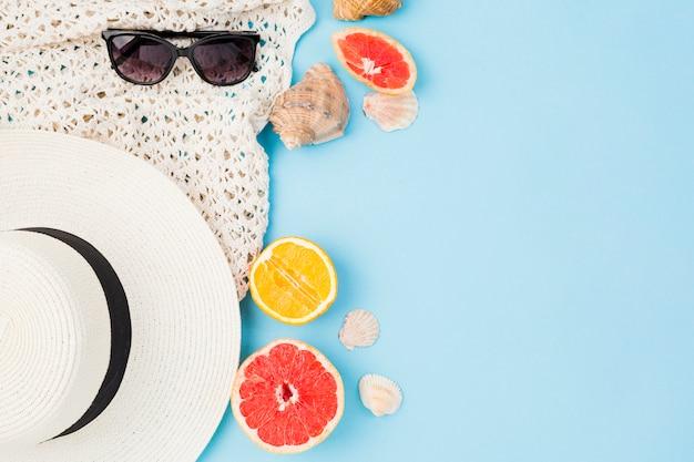 Sombrero de verano y gafas de sol cerca de frutas y conchas marinas.