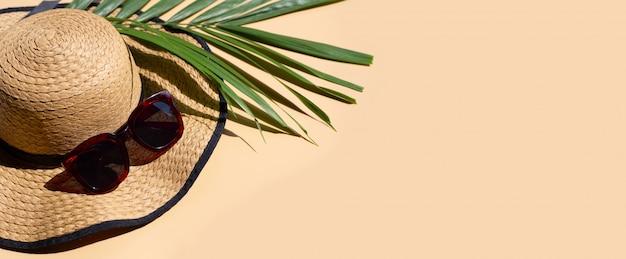 Sombrero de verano con gafas de sol y hojas de palmeras tropicales sobre fondo marrón.