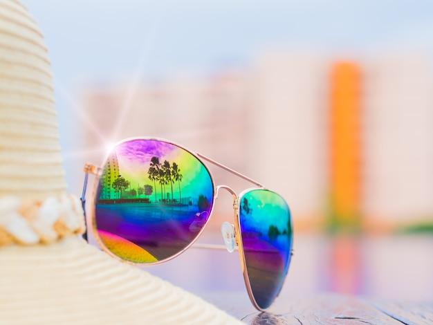 Sombrero de verano y gafas de sol junto a la piscina.