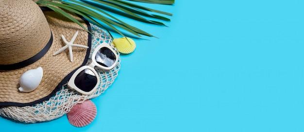 Sombrero de verano con gafas de sol sobre fondo azul. disfrute el concepto de vacaciones.