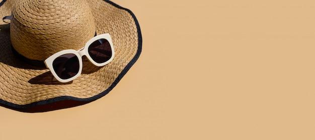 Sombrero de verano con gafas de sol sobre fondo marrón. disfrute el concepto de vacaciones.