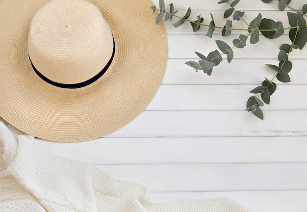 Sombrero de verano y hojas de eucalipto sobre mesa de madera blanca.
