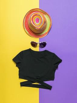 Sombrero de verano multicolor, camiseta negra y gafas sobre una superficie bicolor