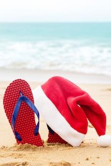 Sombrero y zapatos de santa en el océano arenoso. concepto de navidad