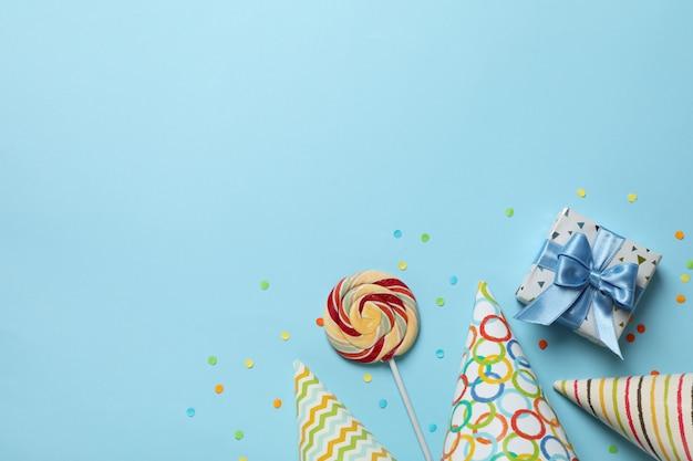 Sombreros de cumpleaños, caja de regalo y piruleta sobre fondo azul, espacio para texto