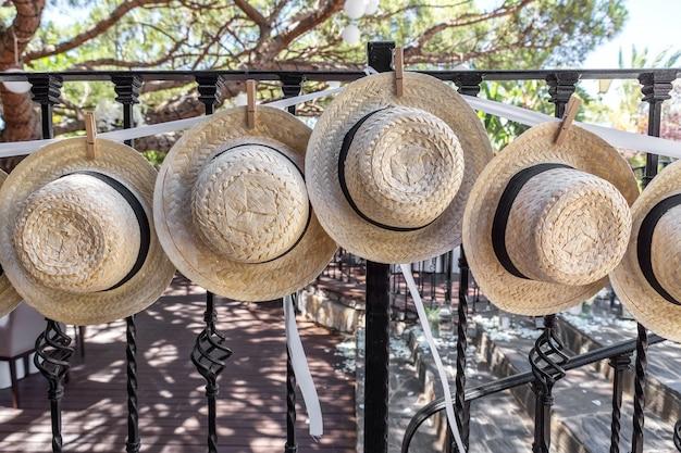 Sombreros de paja para la decoración de la boda en la valla.
