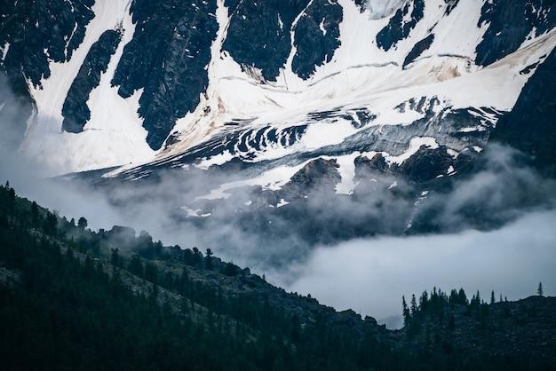 Sombría vista espectacular a la pared de la montaña nevada gigante entre nubes bajas en la noche oscura