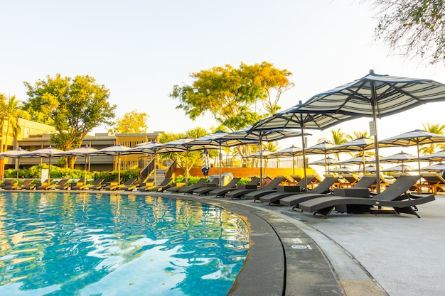 Sombrilla y cama de piscina alrededor de la piscina al aire libre en el complejo hotelero para viajes de vacaciones