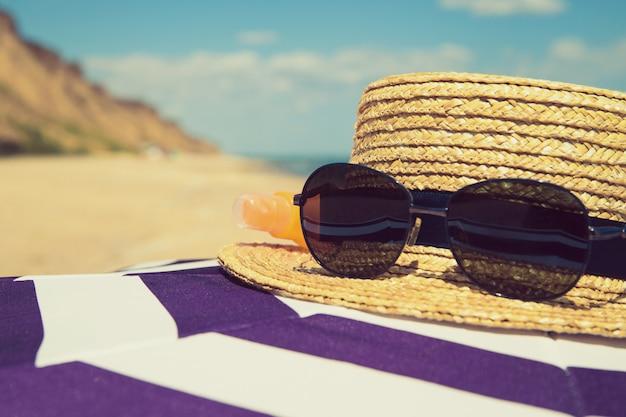 Sombrilla de playa a rayas con sombrero de paja