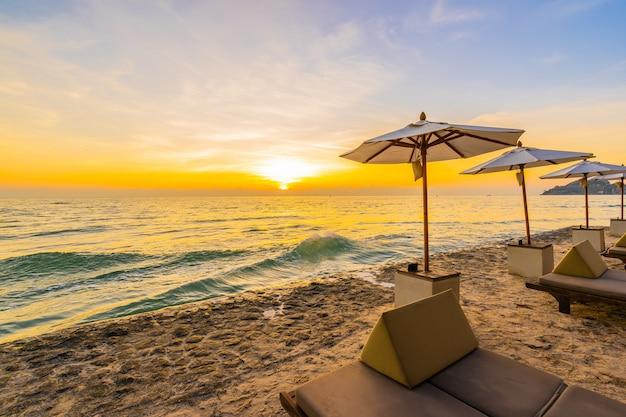 Sombrilla y silla con almohada alrededor del hermoso paisaje de playa y mar.