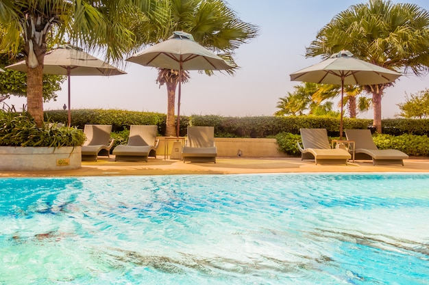 Sombrilla y silla alrededor de hermosa piscina de lujo.