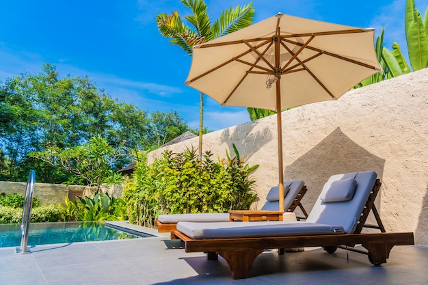 Sombrilla y silla alrededor de la piscina cerca del mar, playa oceánica con cielo azul y nube blanca