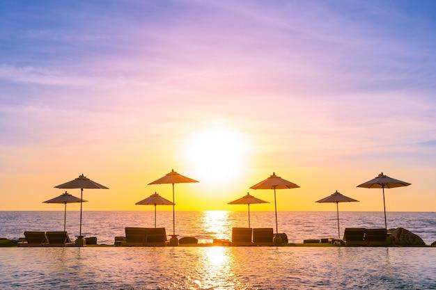 Sombrilla y silla alrededor de la piscina en el hotel resort para viajes de placer y vacaciones