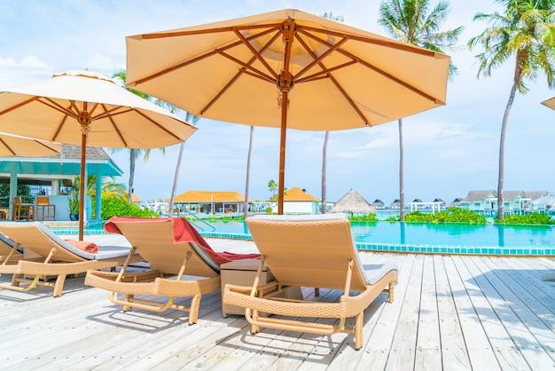 Sombrilla y silla alrededor de la piscina en el hotel resort