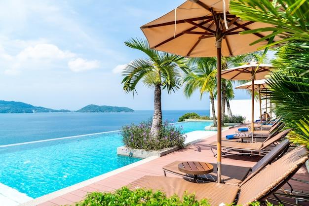 Sombrilla y silla alrededor de la piscina en hotel y resort.