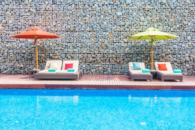 Sombrilla y silla alrededor de la piscina.