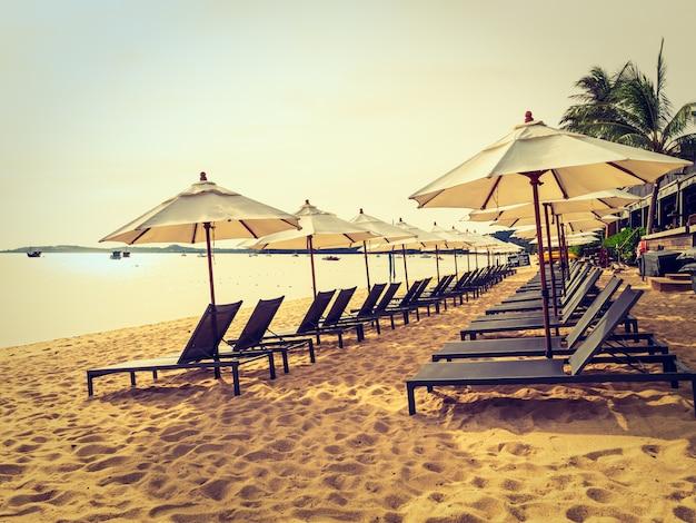 Sombrilla y silla en la playa tropical mar y océano al amanecer