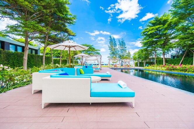 Sombrilla y tumbona alrededor de la piscina