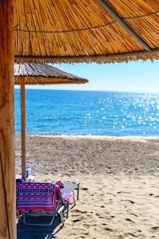 Sombrillas de caña y tumbonas en la playa vacía
