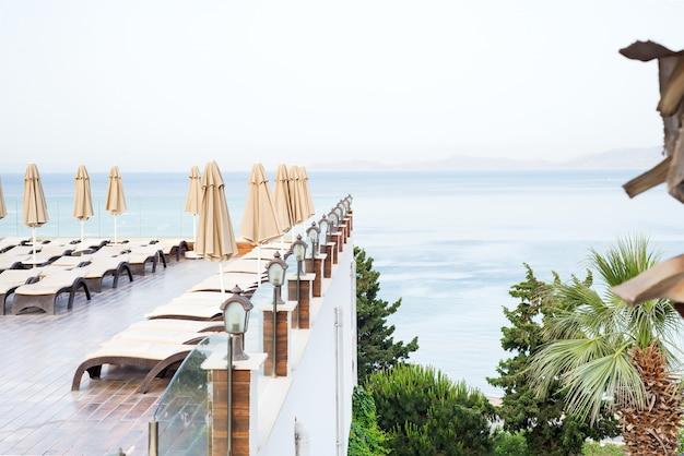 Sombrillas de color beige y tumbonas junto a la piscina con vistas al mar.