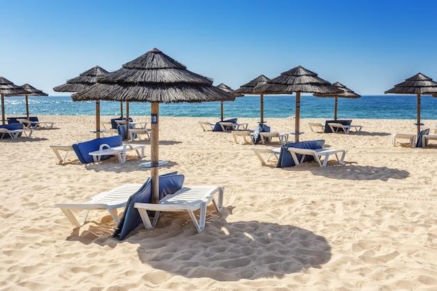 Sombrillas y tumbonas en la playa sur del algarve. portugal.