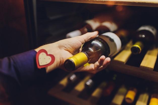 Sommelier con botella de vino cerca del estante en la tienda.