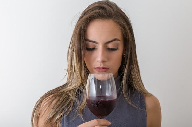 Sommelier concentrado de la mujer joven con el vino rojo en vidrio sobre el fondo blanco