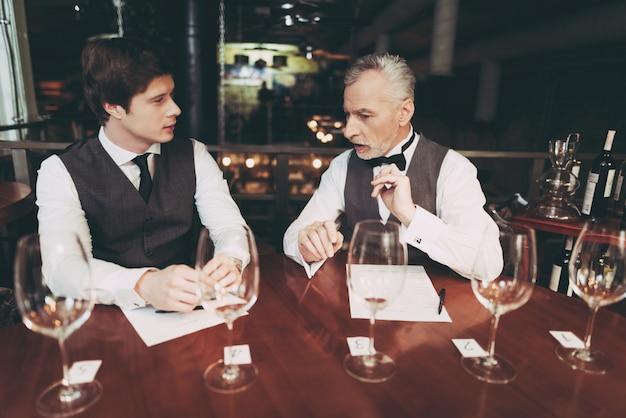 Sommelier confidente hace carta de vinos en el restaurante.