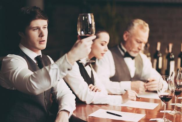 Sommelier experimentado mira sedimento de vino en vidrio.