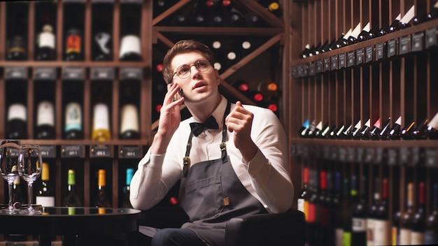 Sommelier está hablando en un teléfono inteligente, sentado en una mesa en el fondo de bastidores de botellas de vino
