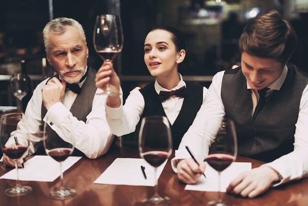 Sommeliers es dos hombres y una mujer en el restaurante.