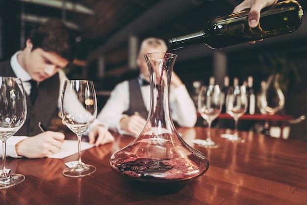 Sommeliers está escribiendo notas sobre las cualidades de sabor del vino.