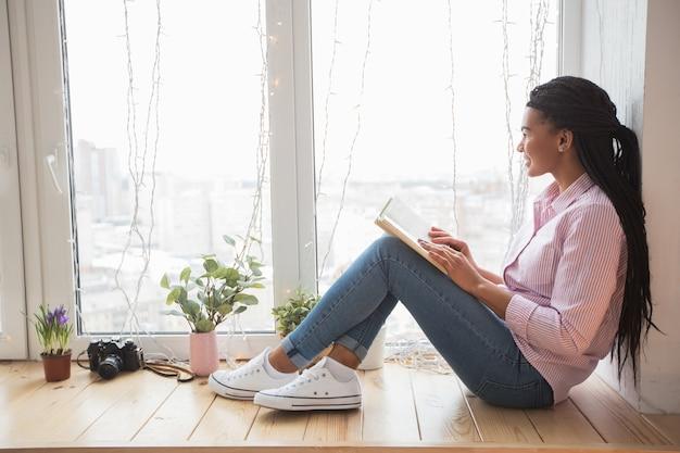 Soñadora estudiante con libro sentado en el alféizar de la ventana