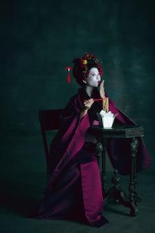 Soñadora. joven japonesa como geisha aislada en la pared de color verde oscuro. estilo retro, comparación del concepto de eras. modelo femenino hermoso como personaje histórico brillante, anticuado.