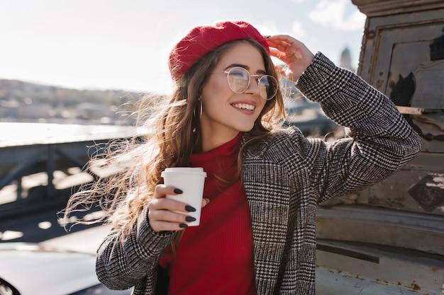 Soñadora mujer francesa de pelo largo con gafas mirando a otro lado con una sonrisa, sosteniendo una taza de café