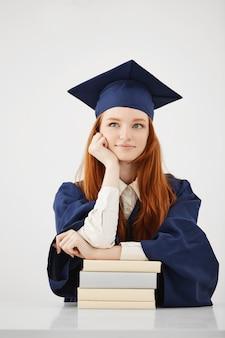 Soñadora mujer graduada sonriendo pensando sentado con libros sobre superficie blanca