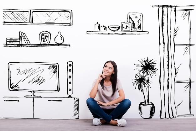 Soñando con apartamento nuevo. mujer joven alegre sonriendo mientras está sentado en el suelo