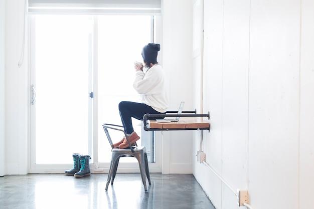 Soñando mujer tomando café en la oficina en casa
