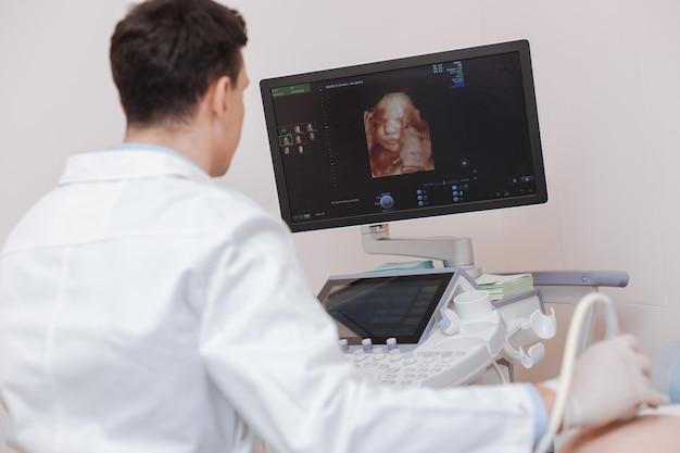 Sonógrafo profesional concentrado y útil que trabaja mientras usa una máquina de ultrasonido para monitorear el vientre de embarazada por ultrasonidos y expresar la concentración