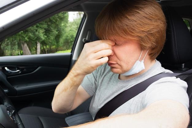Soñoliento conductor de automóvil agotado quitándose la máscara médica