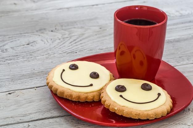 Sonreír galletas en un plato rojo con una taza de café, fondo de madera, comida