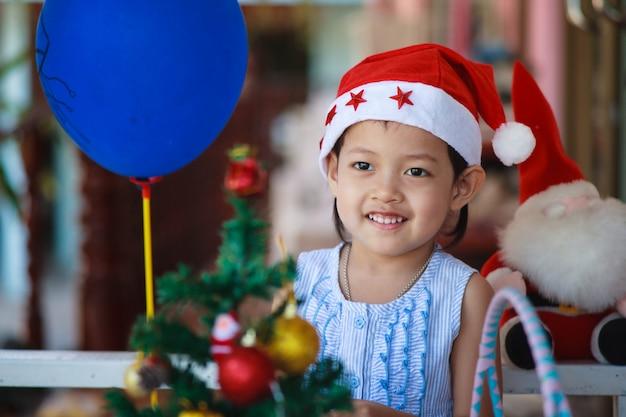 Sonríe niña santa sombrero presente tiene navidad.