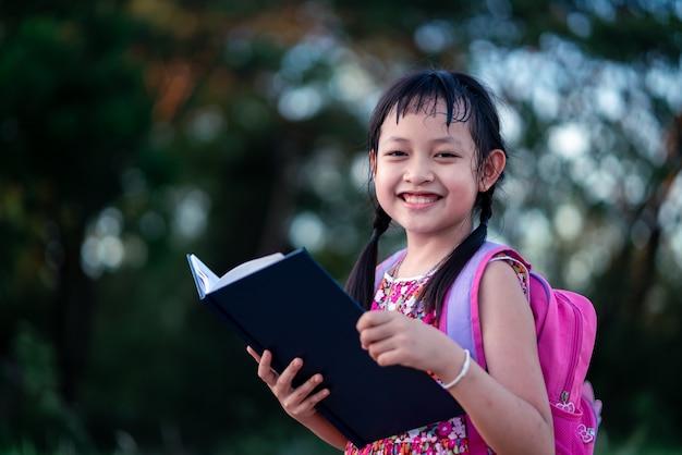 Sonríe pequeño libro de lectura de colegiala con mochila.volver al concepto de escuela