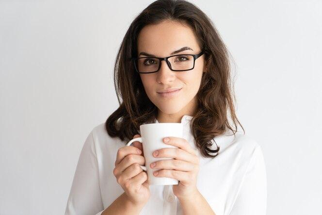 Sonriendo a la mujer bastante joven que sostiene la taza y que mira la cámara.