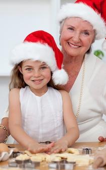 Sonriendo abuela y niña hornear tortas de navidad