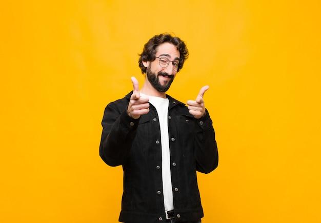 Sonriendo con una actitud positiva, exitosa y feliz apuntando a la cámara, haciendo un signo de pistola con las manos