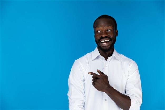 Sonriendo afroamericano barbudo en camisa blanca sobre fondo azul está mostrando algo
