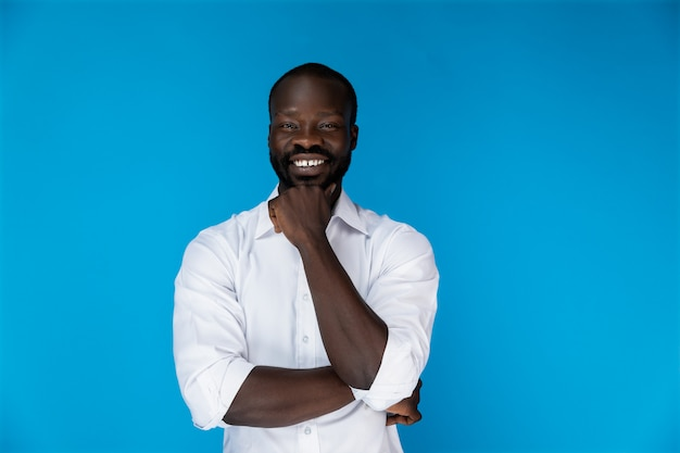 Sonriendo afroamericano en camisa blanca sobre fondo azul