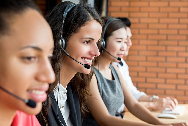 Sonriendo agentes de servicio al cliente de telemercadeo multiétnico, concepto de trabajo de call center