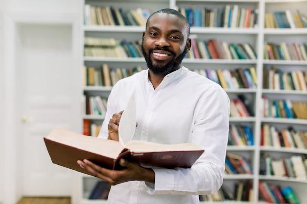 Sonriendo alegre estudiante universitario afroamericano masculino de pie en el moderno salón de lectura de la biblioteca de la universidad, sosteniendo un libro abierto